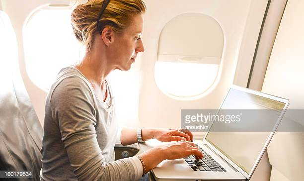 Woman Using Laptop in airplane during flight