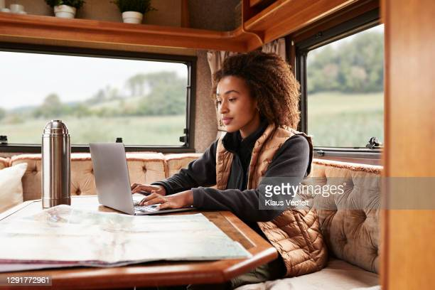 woman using laptop in camper van - holiday stock pictures, royalty-free photos & images