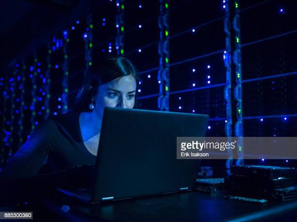 Woman using laptop in dark server room