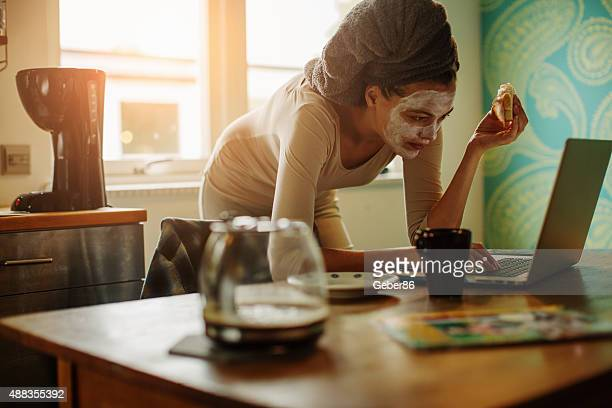 woman using laptop in kitchen - multi tasking stock pictures, royalty-free photos & images