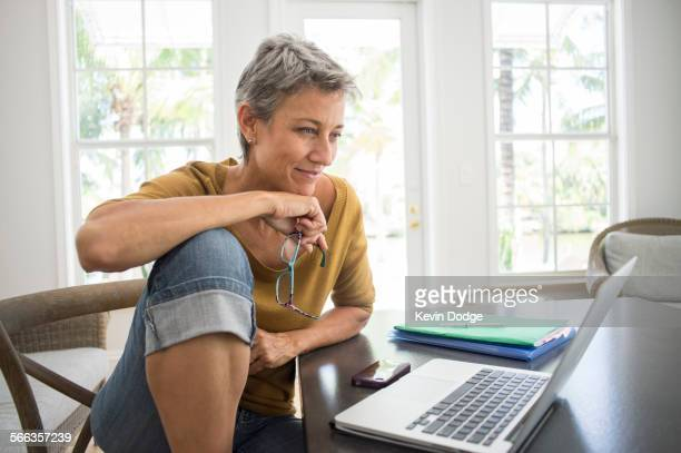woman using laptop in living room - 50 54 years stock pictures, royalty-free photos & images