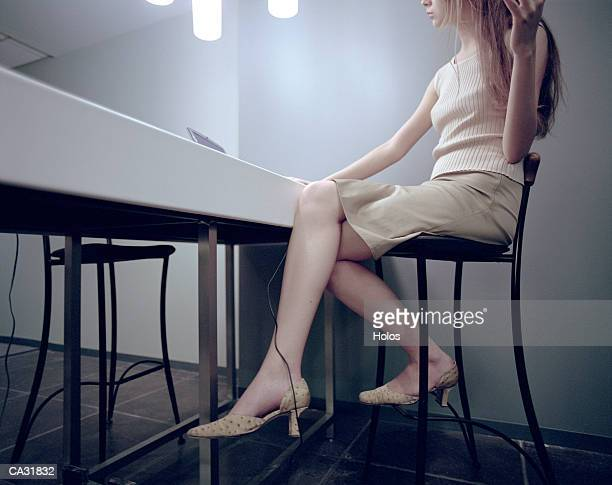 Woman using laptop in office, gesturing with arm, low angle view