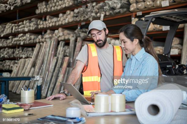 woman using laptop in warehouse with male employee watching - small business stock pictures, royalty-free photos & images