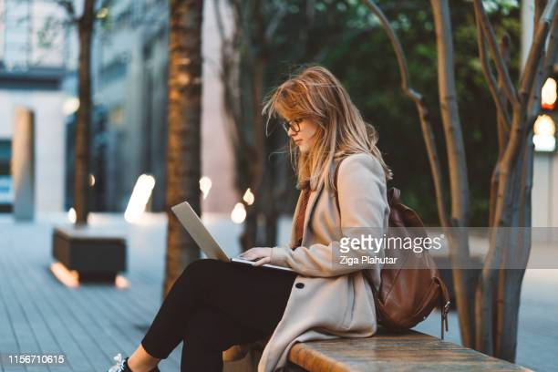 woman using laptop on a bench - science and technology stock pictures, royalty-free photos & images