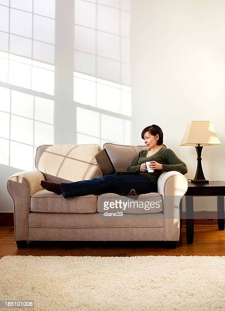 Woman using laptop on a sofa