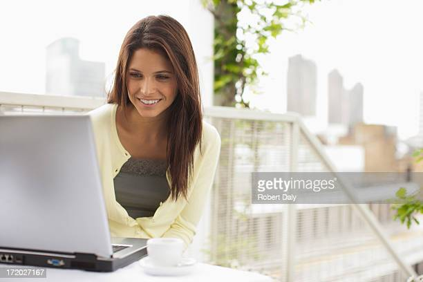 Frau mit laptop auf Balkon