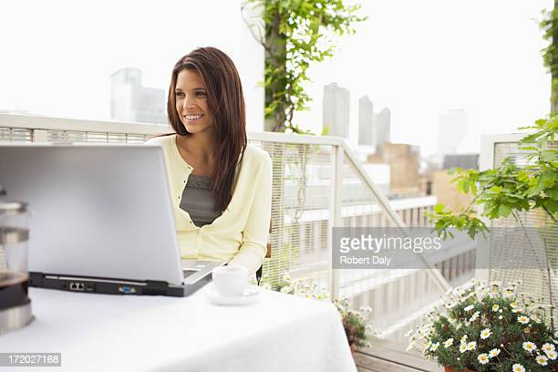 Woman using laptop on balcony