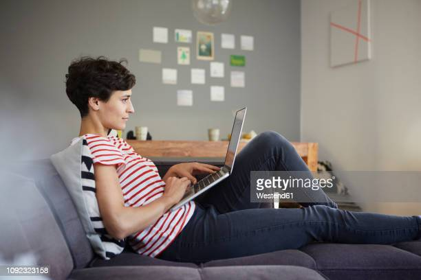 woman using laptop on couch at home - remote work stock pictures, royalty-free photos & images