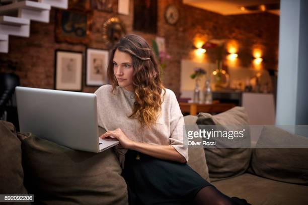 Woman using laptop on couch at home