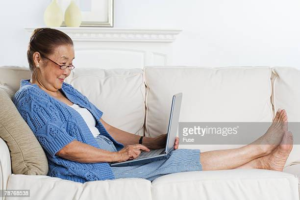 woman using laptop on couch - old lady feet stock pictures, royalty-free photos & images