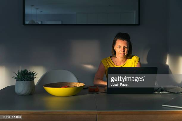 woman using laptop on her dining table at sunset - sun stock pictures, royalty-free photos & images
