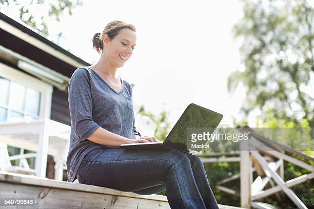 Woman using laptop on porch against clear sky