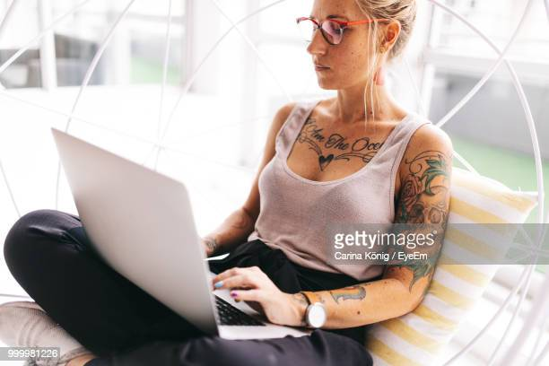 Woman Using Laptop On Seat In Office