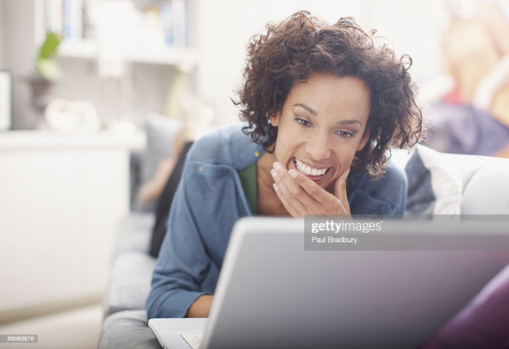 Woman using laptop on sofa : Stock Photo