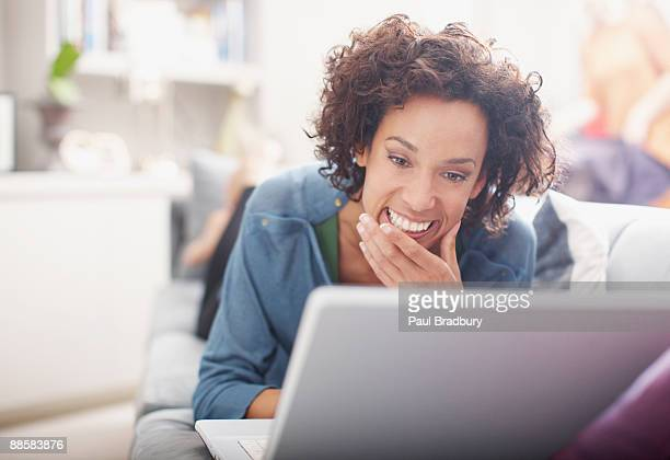 Woman using laptop on sofa