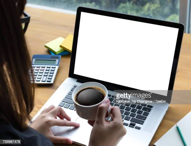 woman using laptop on table - computer screen stock photos and pictures