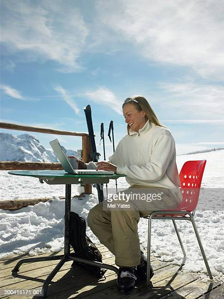 Woman using laptop on terrace, snow covered mountains in background