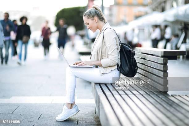 Vrouw met laptop op straat