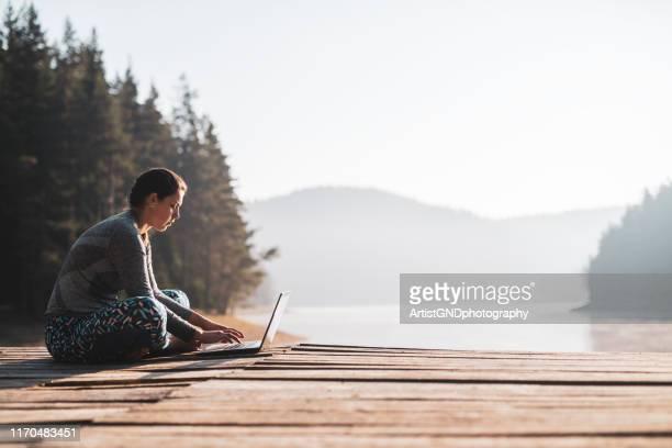 木製の桟橋で屋外でラップトップを使用している女性。 - 人里離れた ストックフォトと画像