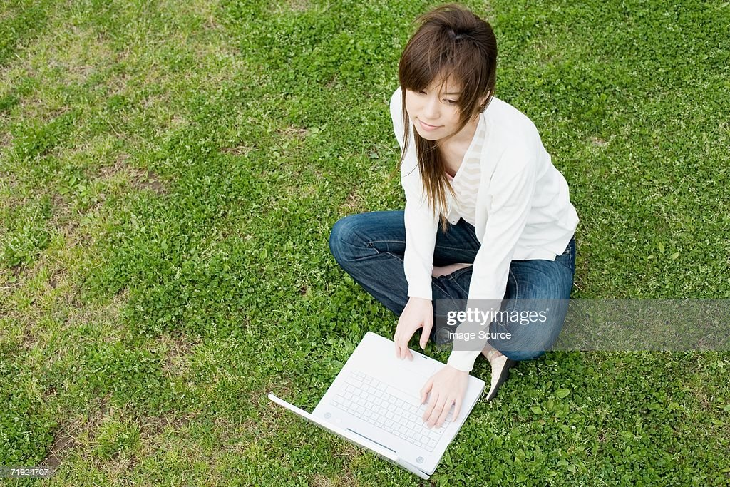 Woman using laptop outdoors : Stock Photo