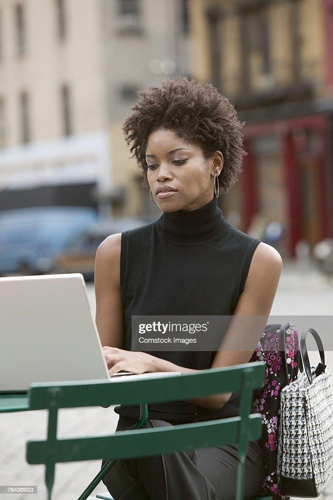 Woman using laptop outdoors : Stockfoto
