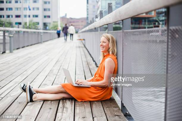 woman using laptop - orange dress stock pictures, royalty-free photos & images