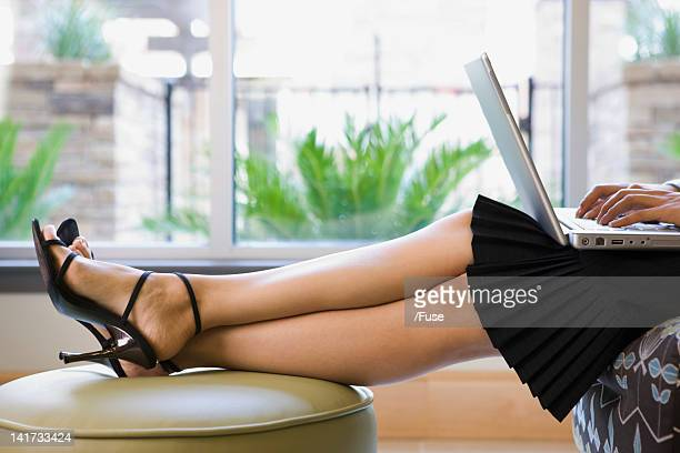woman using laptop - stiletto stock pictures, royalty-free photos & images