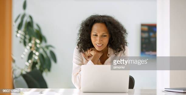 woman using laptop - 40 44 years stock pictures, royalty-free photos & images