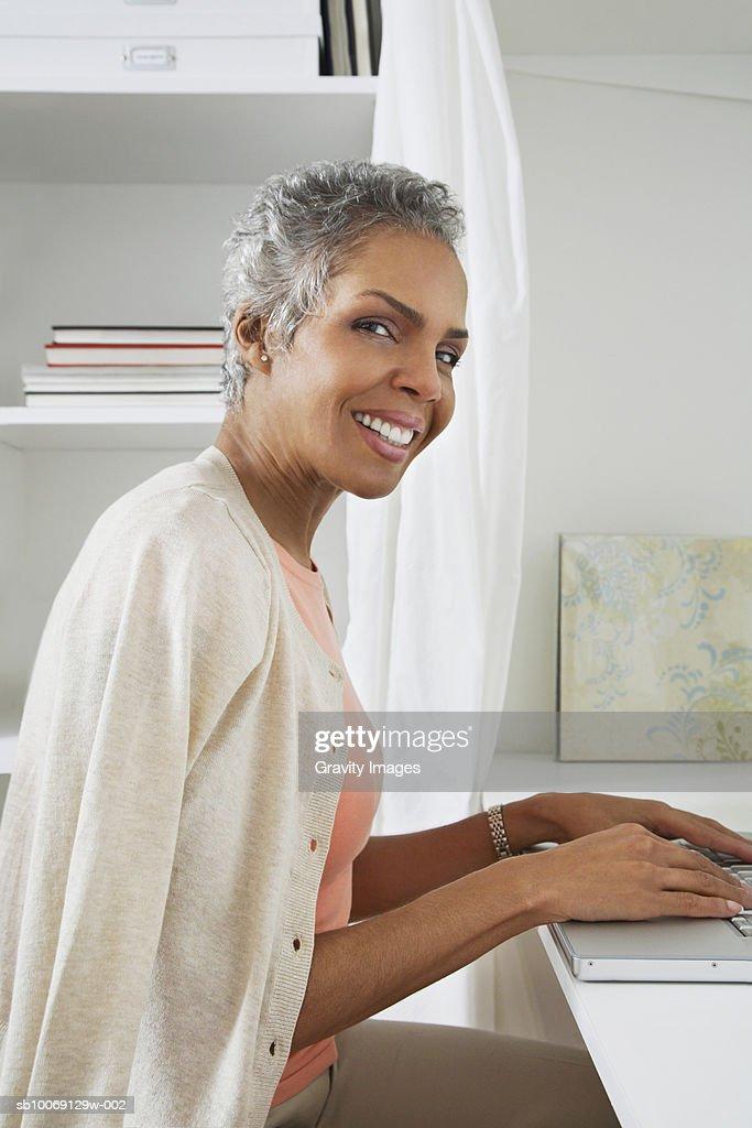 Woman using laptop, smiling, portrait, side view : Stockfoto