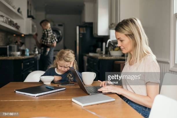 woman using laptop while daughter having breakfast with family in background at home - home icon stock photos and pictures