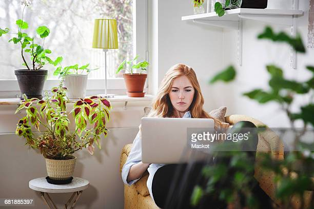 Woman using laptop while lying on chaise longue at home