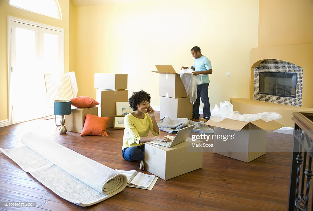 Woman using laptop while man unpacks boxes in unfurnished room : Stockfoto