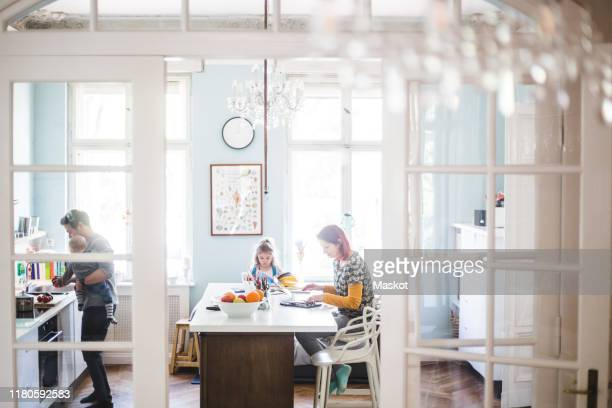 woman using laptop while sitting with girl studying at kitchen island - homeschool stock pictures, royalty-free photos & images
