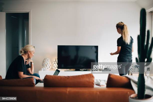 woman using laptop while teenage daughter standing by television set in living room at home - televisión fotografías e imágenes de stock
