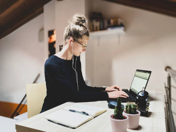 Woman Using Laptop While Working At Desk
