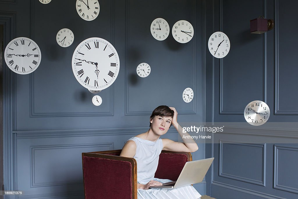 Woman using laptop with hanging clocks above : Stock Photo