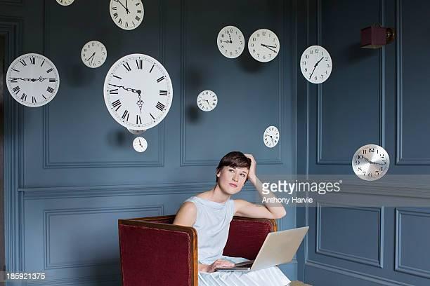 woman using laptop with hanging clocks above - woman hurry stockfoto's en -beelden