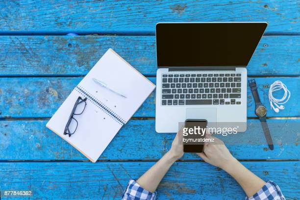 woman using laptop with notepad on table - laptop mockup stock photos and pictures