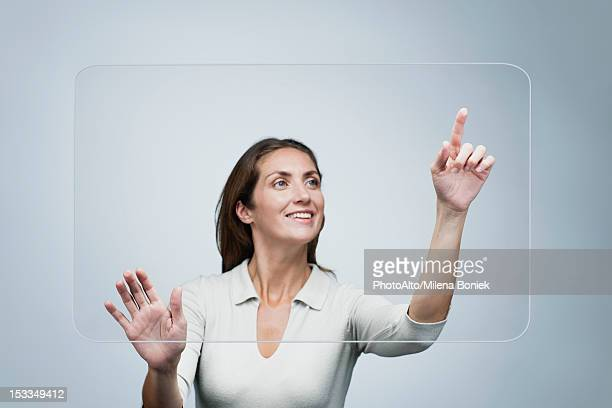 woman using large transparent touch screen - touch screen stock pictures, royalty-free photos & images
