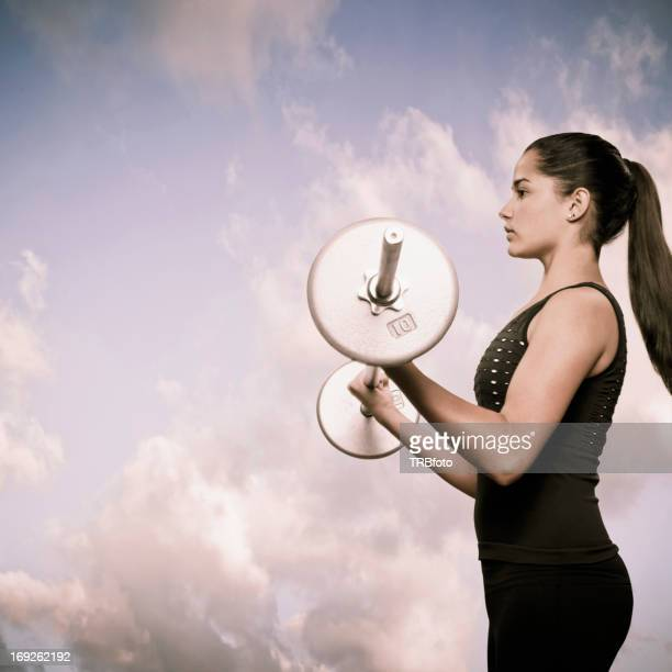 Woman using lifting weights outdoors