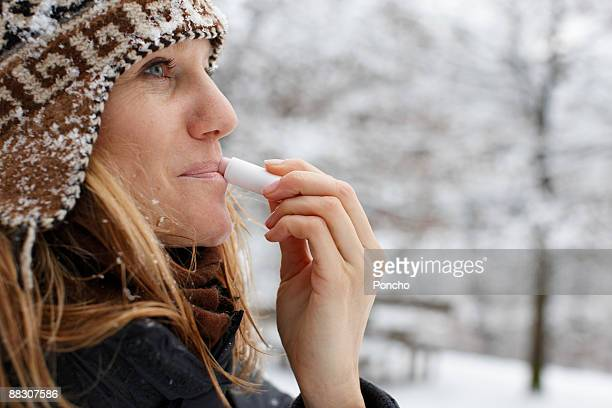woman using lip balm - lip balm stock pictures, royalty-free photos & images