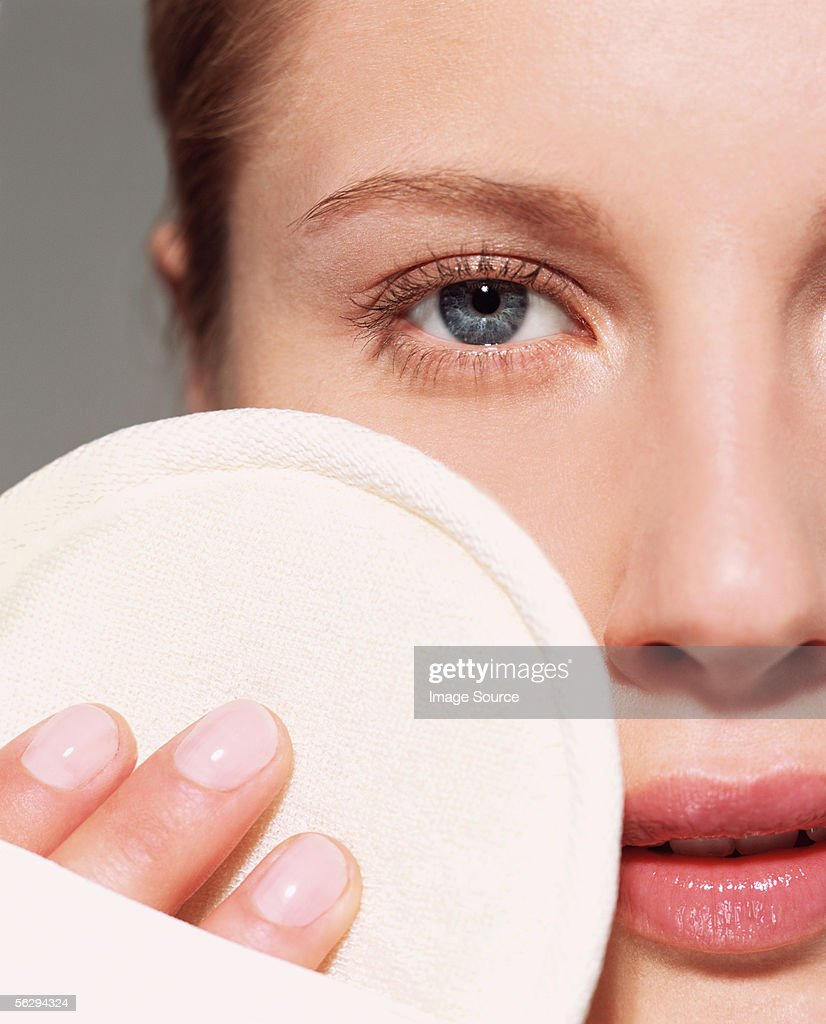 Woman using loofah pad on her face : Stock-Foto