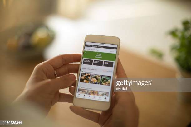 woman using meal delivery service through mobile app. - mobile phone stock pictures, royalty-free photos & images