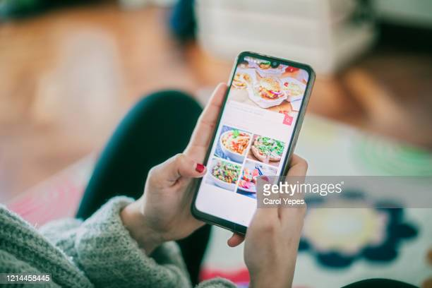 woman using meal delivery service through mobile app. - food delivery foto e immagini stock
