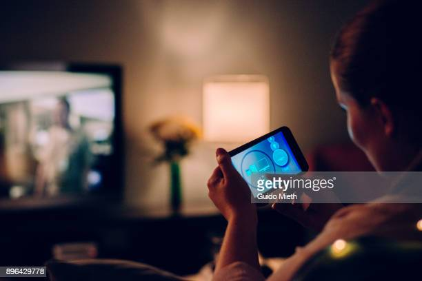 woman using mobile app at home. - tv program bildbanksfoton och bilder