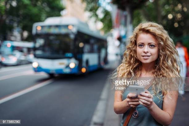 woman using mobile app on bus stop - car pooling stock photos and pictures