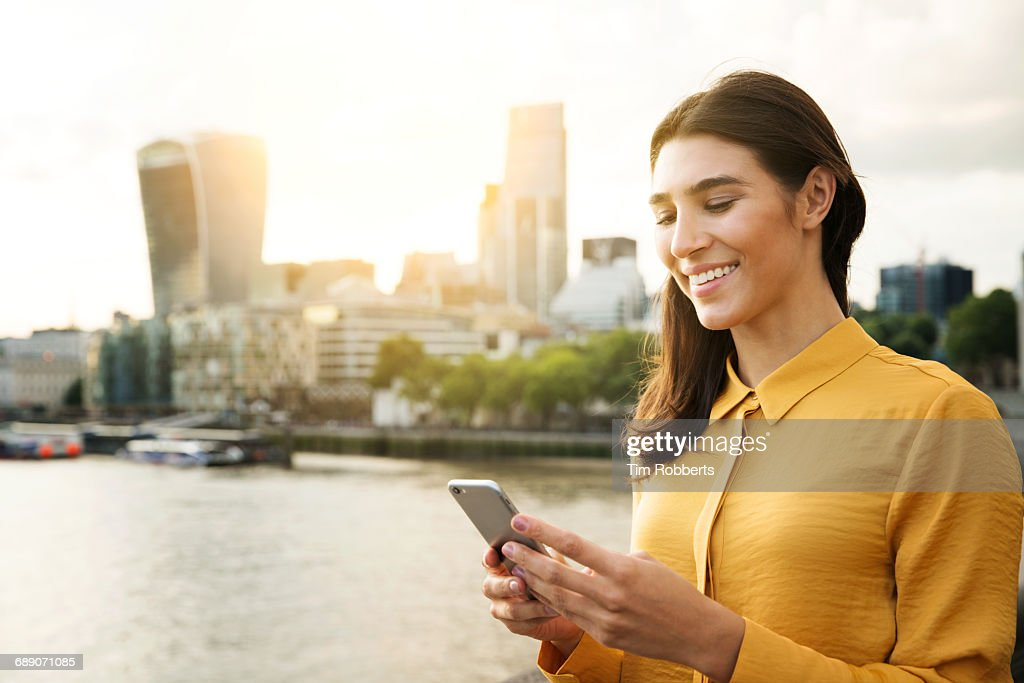 Woman using mobile at sunset : Stock Photo