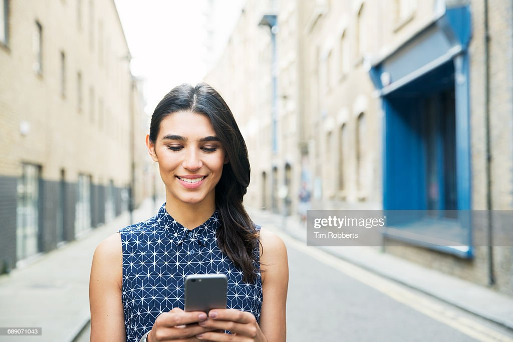 Woman using mobile on street : Stock Photo