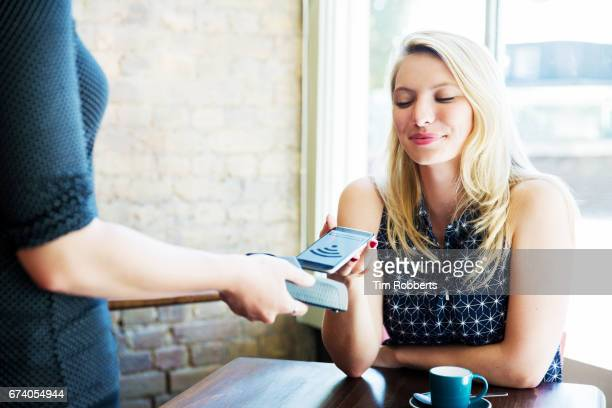 Woman using mobile payment in coffee shop