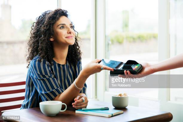 woman using mobile payment in coffee shop - pagando - fotografias e filmes do acervo